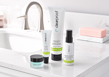 A picture of the three piece Clear Proof® Acne System in white bottles and tubes and Indulge® Soothing Eye Gel in a frosted, translucent pot on a white bathroom counter