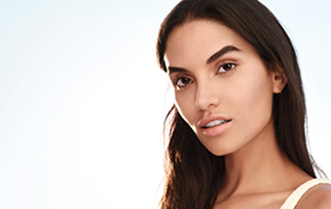 A woman with clear, beautiful skin and dark brown hair poses to promote Mary Kay skin care.