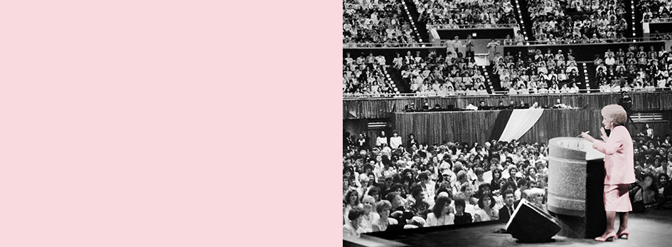 Mary Kay Ash stands at a podium in front of thousands of women at Mary Kay's annual Seminar, a gathering of the independent sales force.